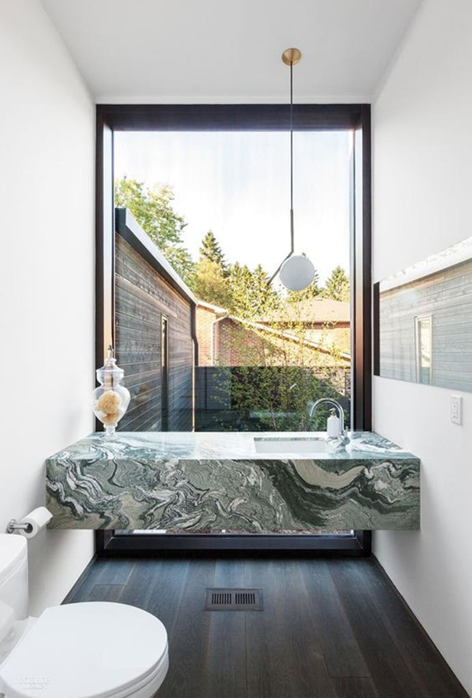 """A green marble bathroom vanity featuring swirls of white complements the all-white aesthetic in this bathroom. *[Interior design via Pinterest](https://www.pinterest.com.au/pin/482940760030204233/