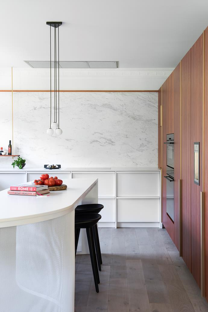 A wall of tall cabinets houses the oven, integrated fridge, freezer and pantry. This keeps the other walls free of overhead cabinets, which helps to maximise the level of filtered light and makes the space feel larger.