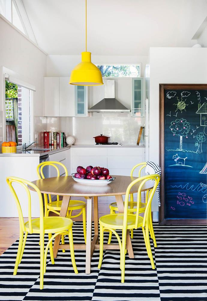 "Yellow dining chairs, accented by a yellow pendant light have given this [Californian Bungalow](https://www.homestolove.com.au/decorating-with-primary-colours-a-bold-bungalow-makeover-3587|target=""_blank"") a colourful and personality-filled makeover. *Photo: Maree Homer*"