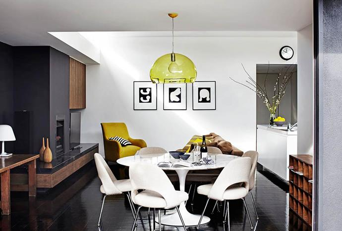 "The transparent yellow pendant light in this cool [inner-city villa](https://www.homestolove.com.au/inner-city-villa-with-a-timeless-cool-appeal-3509|target=""_blank"") gives the living room a soft glow, while the statement arm chair adds a touch of colour to the monochromatic décor. *Photo: Sharyn Cairns*"