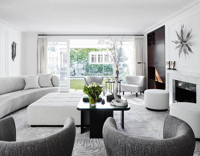 The living area was designed with space in mind. Wall sconce in brushed steel from Two Is Company and sculpture above fireplace from Talisman London. Circular chairs in 'Larsen' fabric from Space. Rug by Poco Designs and made by Designer Rugs.