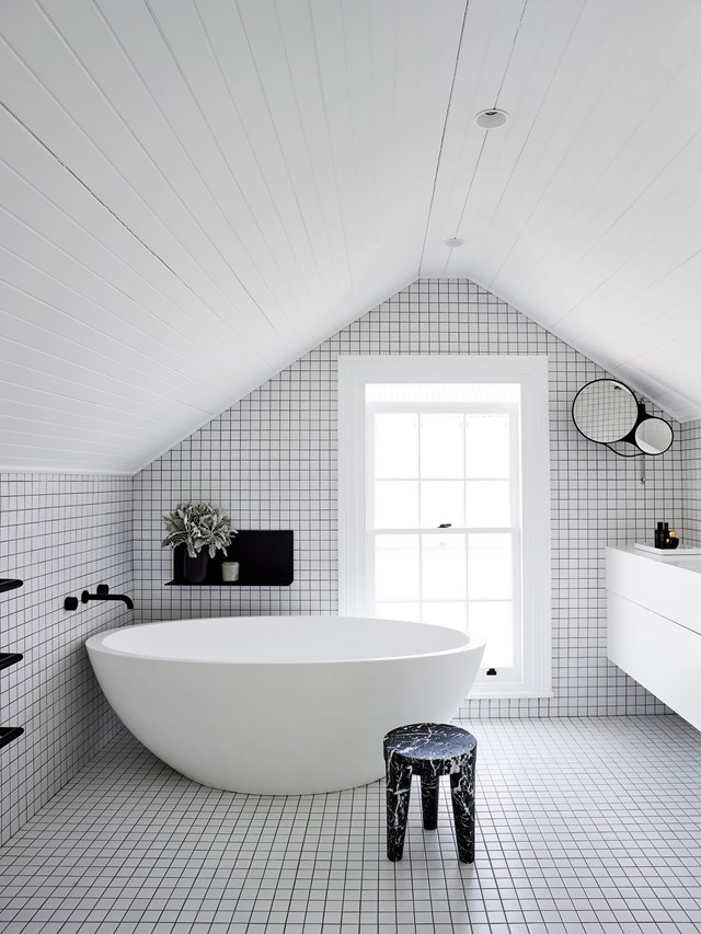 "This edgy black and white bathroom in a [chic inner city terrace](https://www.homestolove.com.au/chic-makeover-of-an-inner-city-terrace-6331|target=""_blank"") just wouldn't be complete without the generously-sized freestanding bath tub. *Photo: Anson Smart*"