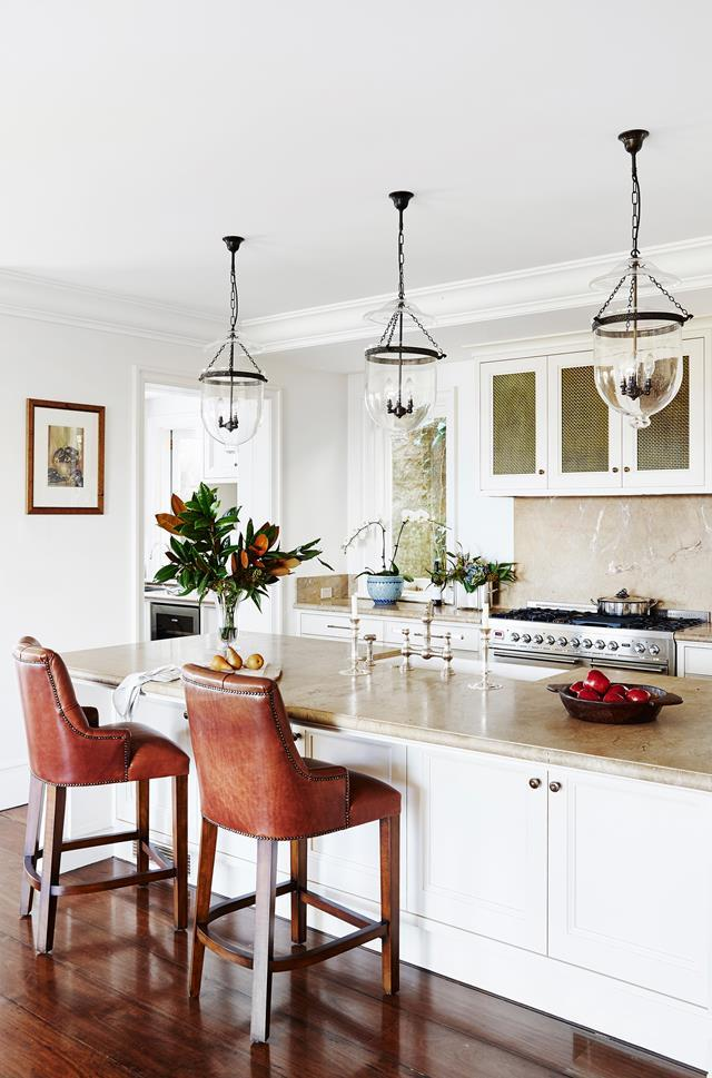 "French provincial meets Hamptons style in this entertainers' kitchen. The [three-storey home in Sydney's eastern suburbs](https://www.homestolove.com.au/french-provincial-home-in-sydney-5418|target=""_blank"") fuses soft neutral hues, rustic bar stools and a trio of glass pendant lights. *Photo: John Paul Urizar / Story: Australian House & Garden*"