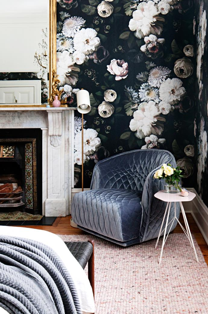 In the main bedroom, 'Dark Floral' wallpaper by Ellie Cashman blends into the original 19th-century marble fireplace. Moroso 'Redondo' armchair by Patricia Urquiola. Anta 'Nobu' floor lamp by Carsten Gollnick.