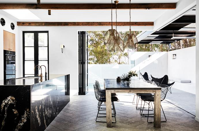 The island bench is in polished black granite. The dining table from Restoration Hardware has a reclaimed timber base and a zinc top and is paired with Knoll 'Bertoia' chairs. Wall lights from Visual Comfort.