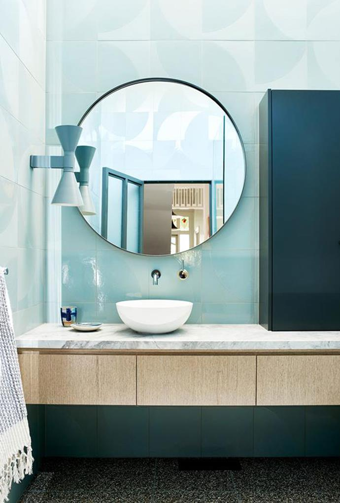 This blue wall light was chosen due to its shapely form and subtle glow, however, is not typically used in bathrooms. *Photography: Mark Roper*