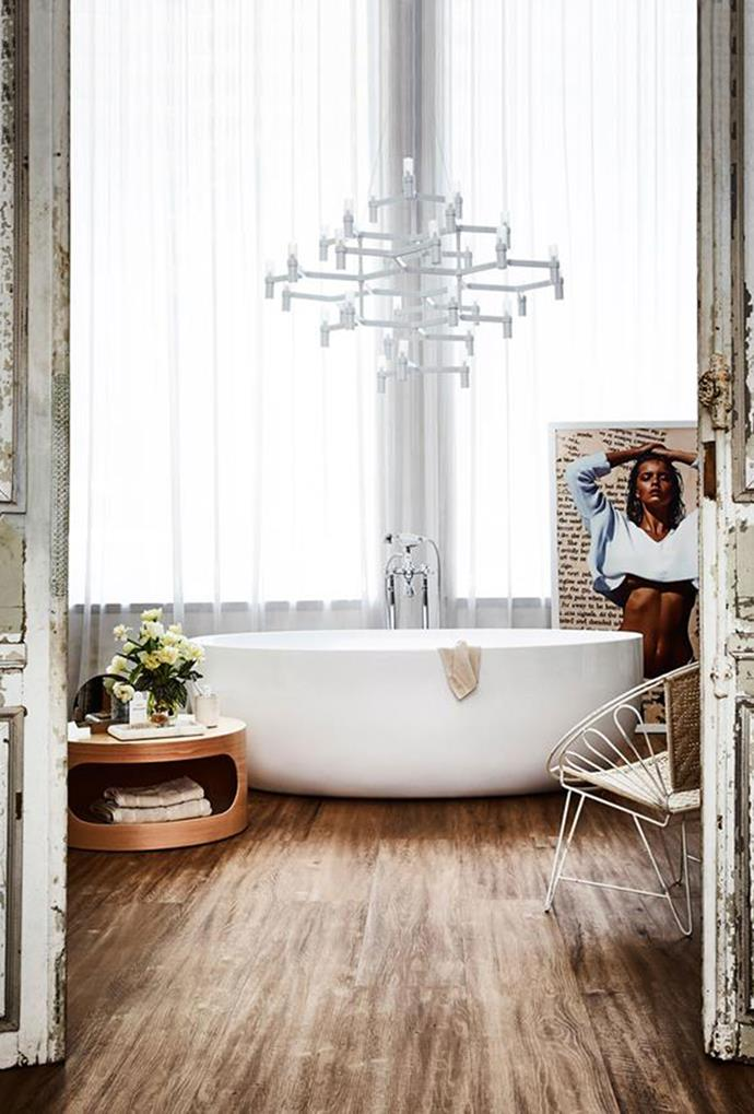 A contemporary white chandelier was used in this bathroom to create an element of structure, among an otherwise rustic aesthetic. *Photography: Kristina Soljo*
