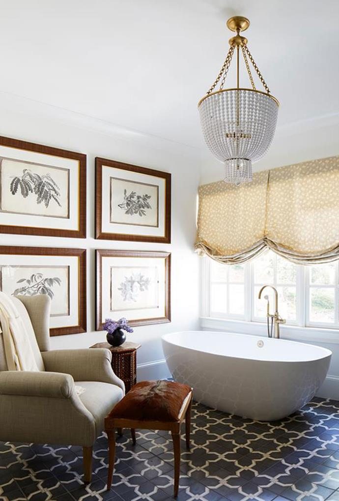 A softly contoured vintage chandelier adopts both a traditional and modern interior perspective in the bathroom of this rustic style home. *Interior design: Shayleyn Woodberry*