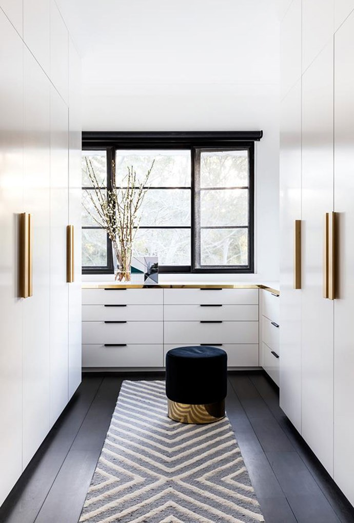 Gold cabinetry accents, together with a statement rug and stylish ottoman create a dreamy walk-in wardrobe space. *Photo: Pablo Veiga | Story: Belle*