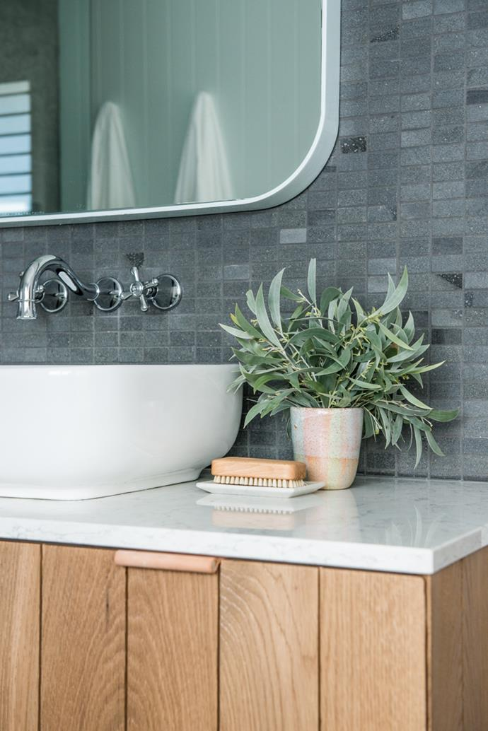 The scandi-style bathroom is complemented by a touch of greenery. *Photo: supplied*