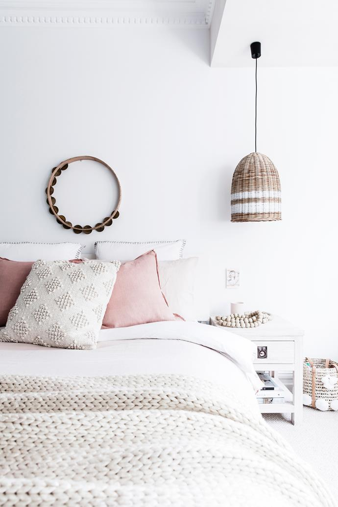 Each of the bedrooms features a white base palette, accented with a subdued hue, like this pink.