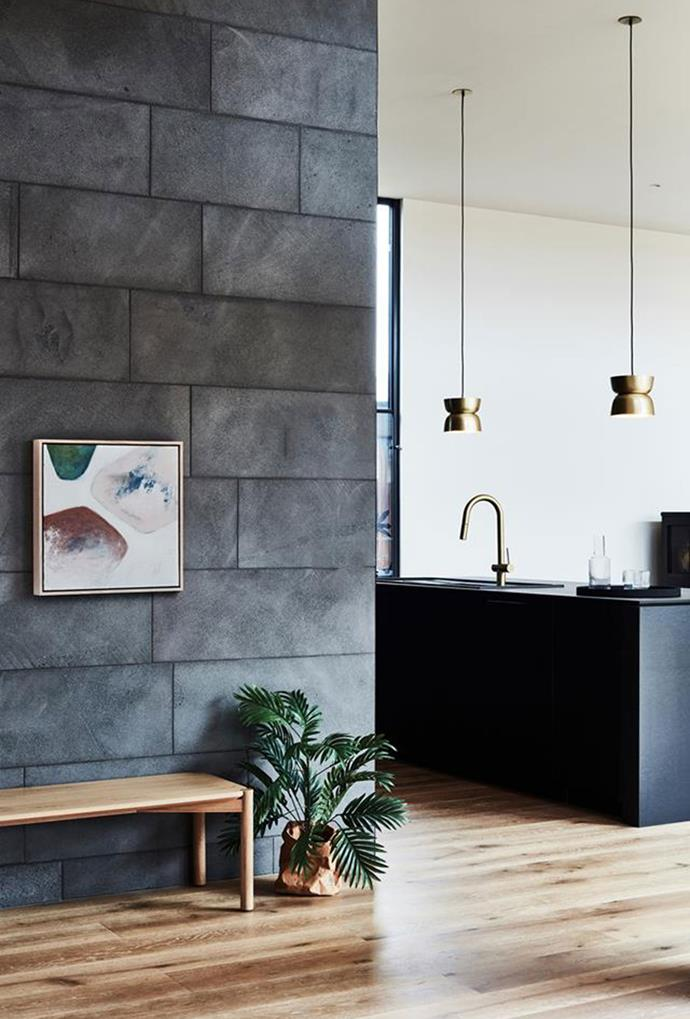 "Small brass pendant lights, paired with brass tapware, are contrasted to the mostly black colour palette in the kitchen of this [Barwon Heads home](https://www.homestolove.com.au/architecturally-designed-ready-to-build-home-5985|target=""_blank""). Their placement also makes for a functionally lit kitchen bench."