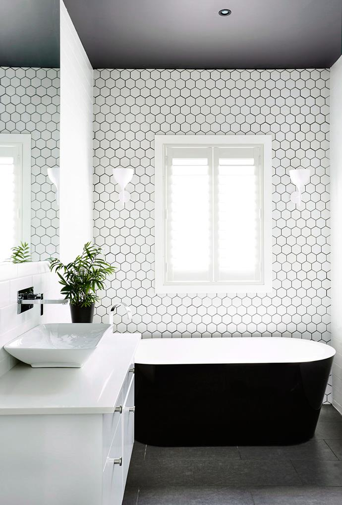 Clever use of tiles can add to the overall effect of your bathroom, as well as its functionality. Here, geometric shapes create a statement feature wall — no colour required.