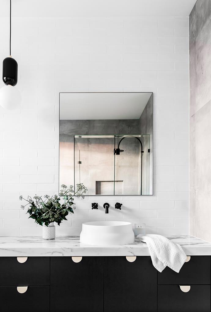 A rendered concrete wall adds a welcome contrast to this otherwise black and white space. Ticking boxes in both style and durability, this parred-back bathroom would work well all kinds of styling options.