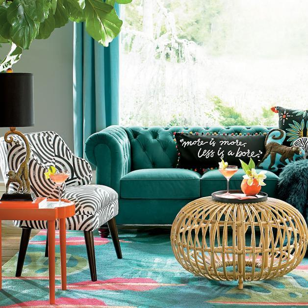 Round Rattan Cocktail Ottoman, $267, and More Is More Pillow, $80.