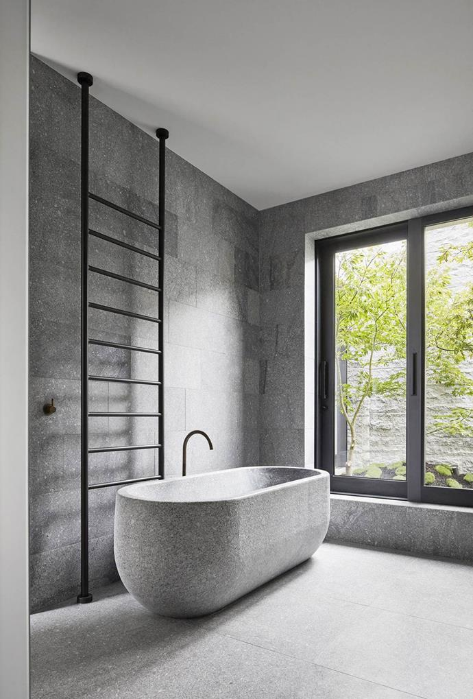 This residential bathroom design features a free-standing stone bathtub, together with matching wall and floor tiles — creating a refined, yet relaxing retreat.