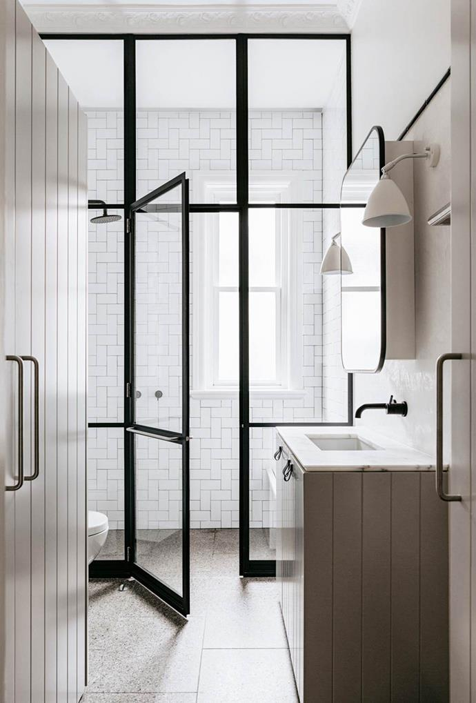 A steel-framed glass wall, fitted with a door, is used as a partition to shield water in this stylish bathroom. The neutral colour palette also makes for an industrial aesthetic.