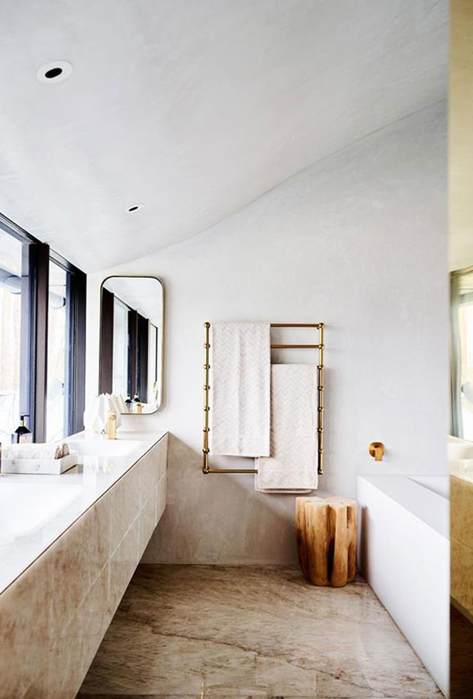 "Marble detailing and rendered walls, treated with stucco for a velvety finish, contrast the precision of brass accents in this [contemporary bathroom](https://www.homestolove.com.au/luxurious-transformation-of-a-former-factory-in-melbourne-6171|target=""_blank""). *Photo: Mark Roper*"