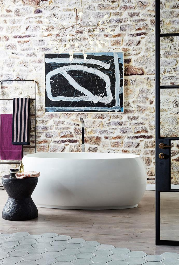 An exposed brick wall, hexagonal tiling and a contemporary artwork all make talking points in this luxurious bathroom space, which is also elevated by a free-standing tub. *Photo: John Paul Urizar*