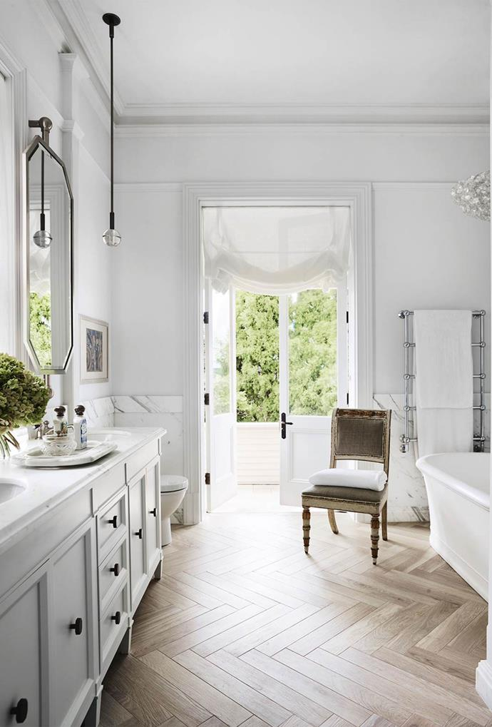 "This grand ensuite by [Thomas Hamel & Associates](https://thomashamel.com/|target=""_blank"") was given a glamorous makeover. The inclusion of marble wall panelling, faux wood ceramic floor tiles and contemporary crystal light fittings challenge traditional expectations of a bathroom aesthetic. * Photo: Anson Smart*"