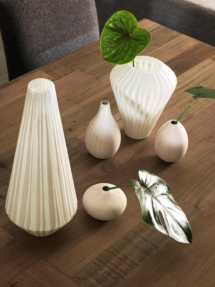 "**Art meets table:** ""Create an art installation on your dining table by pairing together vases in clean, sculptural shapes that complement each other. The pairing of floral arrangements with classic natural wood tones really allows their natural beauty to shine,"" says McCabe."