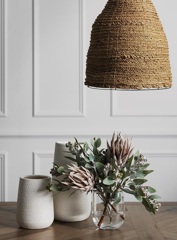 "**Flower power:** ""Match your flowers to your décor with soft, earthy tones that complement the warm wood stains and organic feel of the sisal pendant and textured vases,"" says Gex."