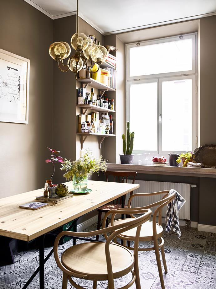The kitchen walls are painted a muted brown that Amelia mixed herself, and offset by handmade patterned tiles, an Ikea timber table and Ton chairs. The antique light fitting came from vintage store Gamla Lampor & Möbler.