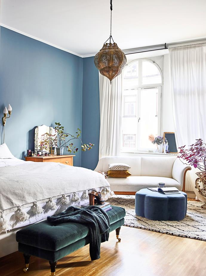 """An """"Ester"""" bench from MeliMeli sits at the foot of Amelia's bed, which is dressed with a Moroccan bedspread."""