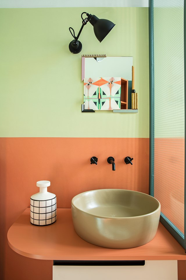 "Tangerine and olive green perfectly complement each other in the bathroom of this [colourful city apartment](https://www.homestolove.com.au/a-colourful-city-apartment-6463|target=""_blank""). Clean lines and simple design is what really makes this colour scheme so successful here. *Photo: Helenio Barbetta / Story: real living*"