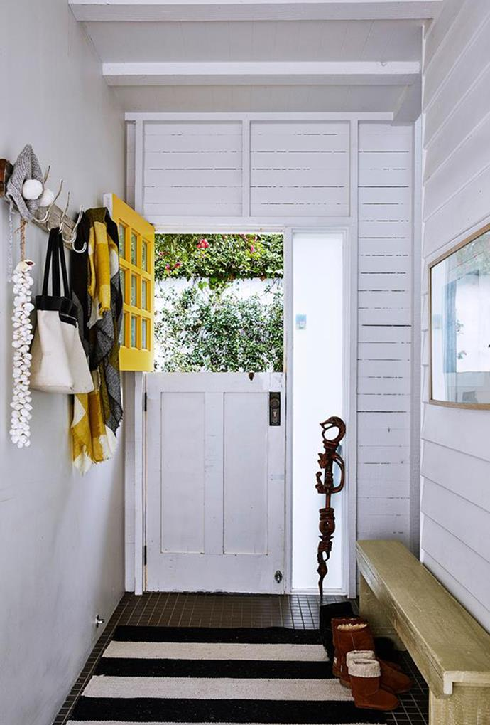 """A stable door with accents of yellow creates a beach-meets-farmhouse feel in this post-war [weatherboard home](https://www.homestolove.com.au/weatherboard-beach-house-sydney-5485