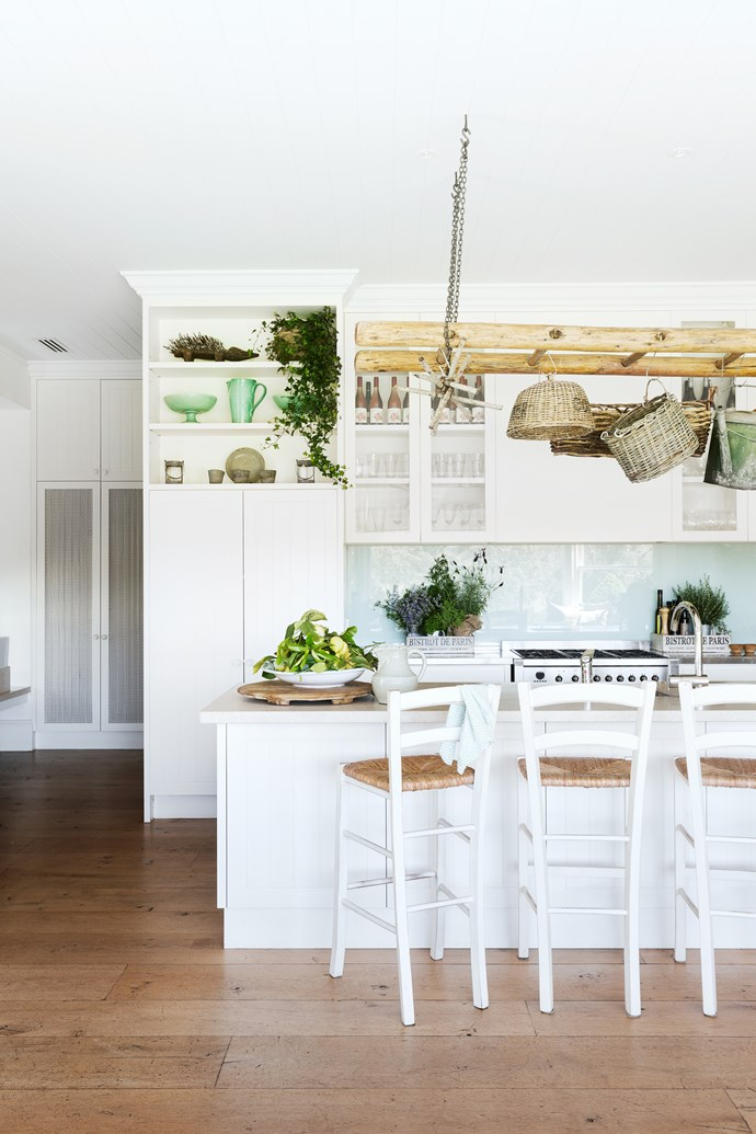 """""""This is such a warm and welcoming room,"""" says designer Adelaide Bragg. """"With checked curtains, natural linens, hanging baskets and a dresser filled with china and trinkets, it epitomises a country kitchen."""" Benchtop, Caesarstone Buttermilk."""