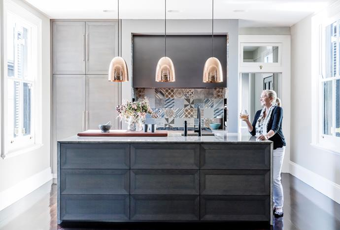 The island bench, made by Wyer+Craw, is finished with a Grigio Cenere marble from Artedomus; its American walnut drawers have a chamfered edge. There's a butler's pantry behind the hall door. Mutina 'Azulej' tiles (splashback) by Patricia Urquiola, Di Lorenzo Tiles. 'Slimline' handles in Rose Gold, MadeMeasure. Designer buy: Original TBC 'Stanley' hammered copper pendant lights, $1628 each (large), Dunlin.