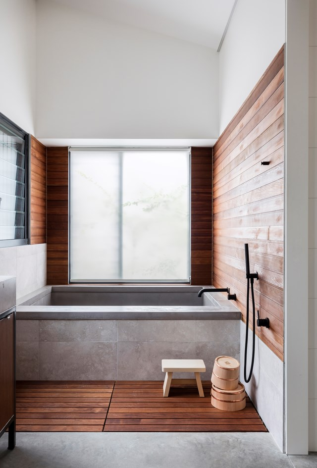 "Clean lines, concrete and rich timber panelling give this [bathroom in a rural New South Wales home](https://www.homestolove.com.au/japanese-style-bathroom-6518|target=""_blank"") a Japanese spa vibe. Natural materials like timber are essential for achieving a minimal, Japanese aesthetic."
