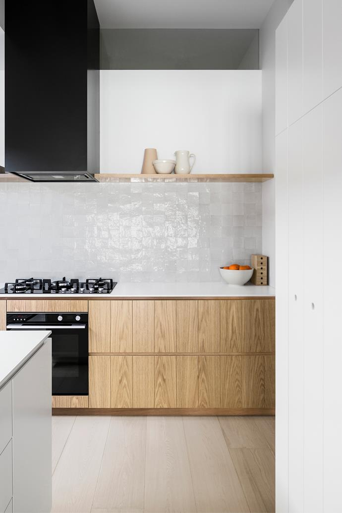 """This tall cabinetry houses a pantry as well as an integrated Fisher & Paykel fridge and freezer. The white joinery is routed with a V-groove detail. """"The grooving helps to conceal door seams and feels less formal,"""" says Carole."""