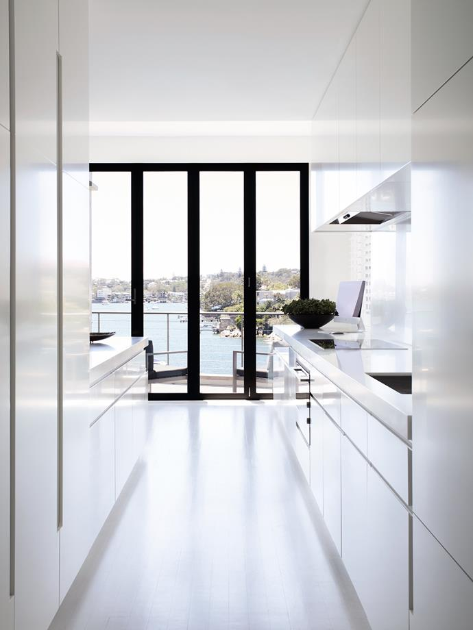 The kitchen is white and minimal, a foil for the decorative ceiling of the dining/living room to which it is connected.