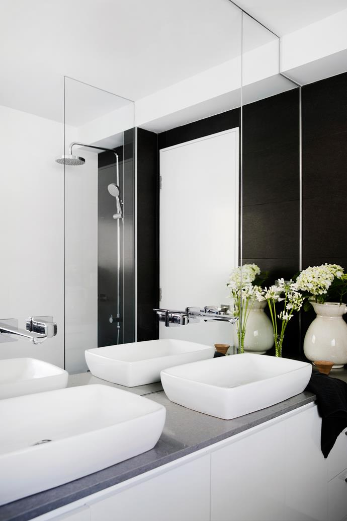 Twin basins meet the needs of four people sharing the bathroom, while the charcoal wall tiles create impact.