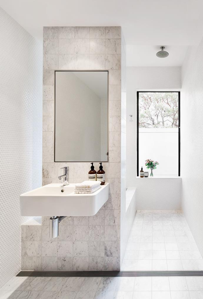 Matte white penny round mosaic tiles, Carrara marble tiles and an open shower combine fun and functionality in this Children's bathroom. *Photo: Murray Fredericks*
