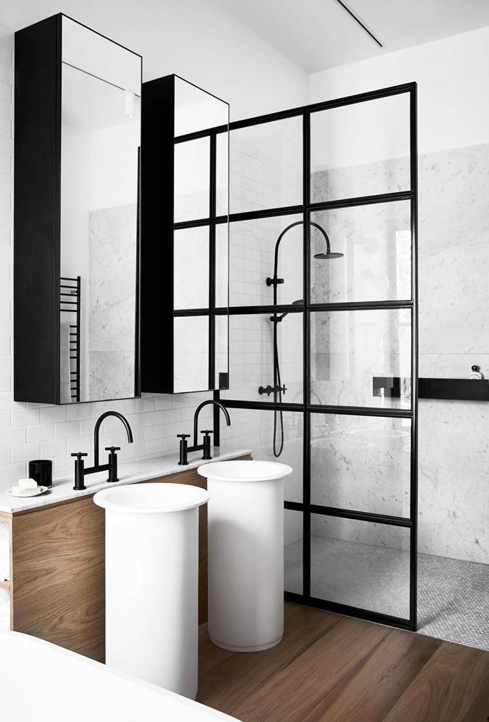 "A steel-framed glass shower screen is used as a partition to shield water in the bathroom of this [sophisticated Melbourne home](https://www.homestolove.com.au/a-light-hearted-luxury-home-3944|target=""_blank""). Accents of marble, wood and black tapware also portray an industrial aesthetic.  *Photo: Carli Philip*"