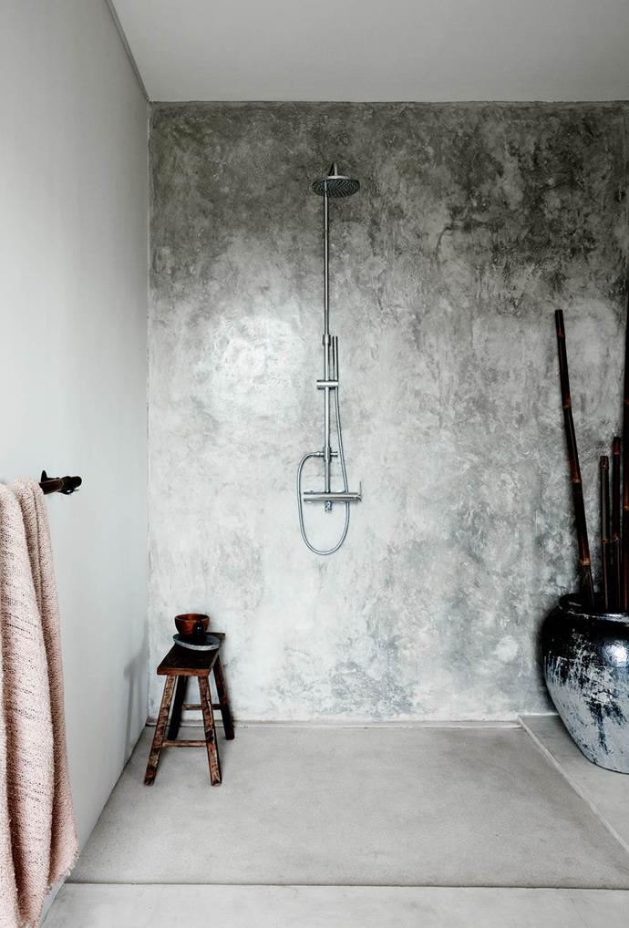 "This [Balinese-style](https://www.homestolove.com.au/a-designer-holiday-home-in-bali-4441|target=""_blank"") cement bathroom is softened with bamboo towel rails and ornamental displays, creating a simple and chic shower space. *Photo: Prue Ruscoe*"