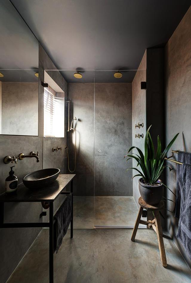 This dark and nocturnal bathroom does not follow normal convention. Instead, the bathroom boasts an intimate and distinct earthiness, where the fixtures are rough, raw and uncomplicated. *Photo: Cameron Spencer*