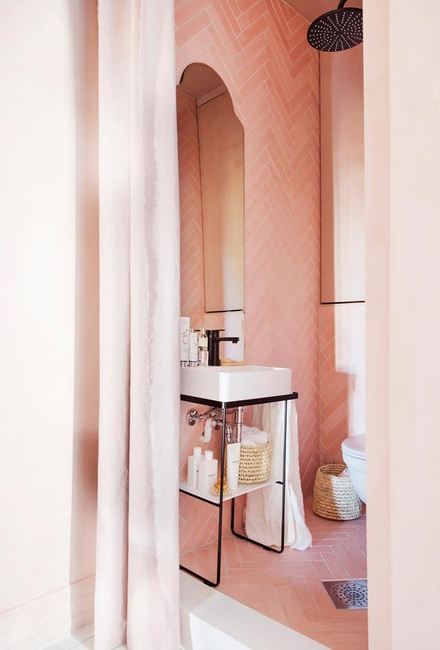 "[Millennial Pink](https://www.homestolove.com.au/millennial-pink-trend-6430|target=""_blank"") subway tiles in a chevron pattern have been laid on the floor and up the walls of this bathroom. The design, which is complemented with black tapware, is reminiscent of a contemporary Scandi aesthetic. *Photo:  Yvonne Wilhelmsen*"