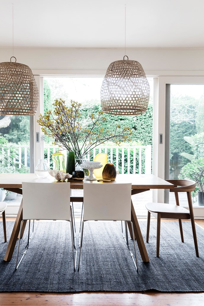 """The table and wooden curve chairs – """"a beautiful design and so comfortable"""" – are from Clickon Furniture, on a rug from Armadillo & Co. Vases from Dinosaur Designs and Country Road."""