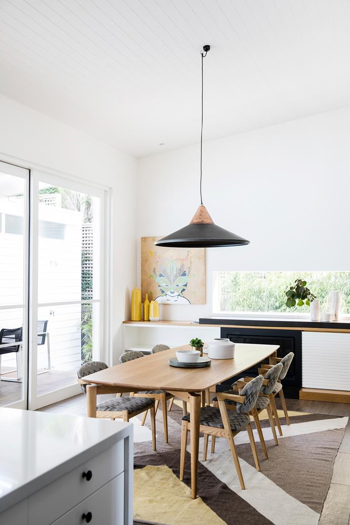 A long, low window draws in green glimpses but blocks out neighbours. Pendant light, Cafe Culture+Insitu. Artwork by Jason Wing. White vases, Sarah Tracton. 'Dusan' dining table, from $6580, Catapult Design.