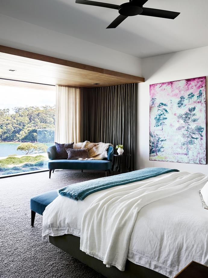 In the main bedroom, Minotti 'Aston' sofa and footstool from De De Ce. Double layered linen curtains, by Simple Studio, conceal wall-mounted TV. Society bedlinen and throw from Ondene. Painting by Tim Summerton from Olsen Gallery.