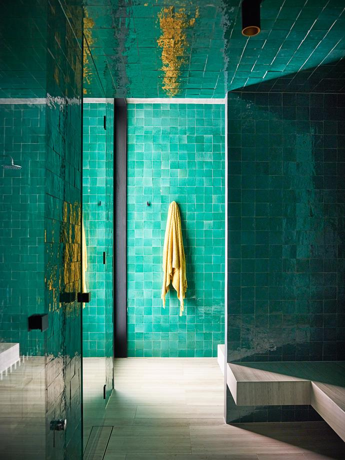 In the steam room, green glazed Moroccan tiles from Onsite. Towel from LuMu Interiors. Flooring and bench seating in silver travertine from SNB Stone.