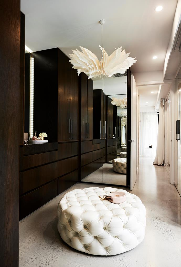 With doors to conceal any mess, this walk-in wardrobe is streamlined and neat, just the way Bec likes it! A pink Chloé Drew bag sits atop the ottoman from Clickon Furniture, while the Icarus pendant light is a standout feature. A Tom Dixon candle vessel is used as a vase (on marble tray).