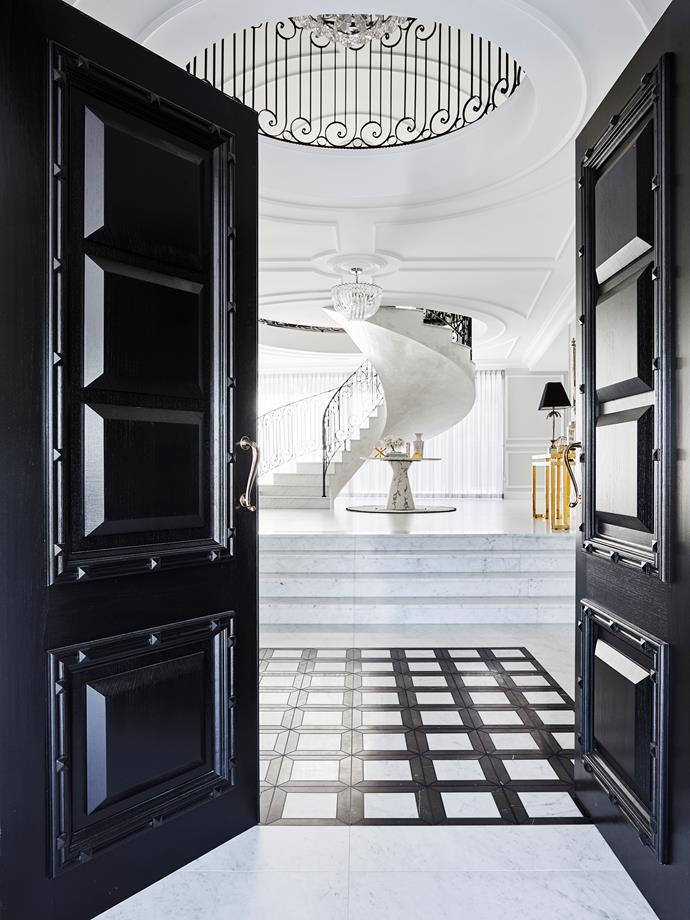 In the hallway, Eichholtz chandelier, console and table. Murano chandelier from Coco Republic. Carrara marble tiles from RMS Marble. Greg Natale Marmo Collection tiles from Teranova. Ceiling details by Allplasta.