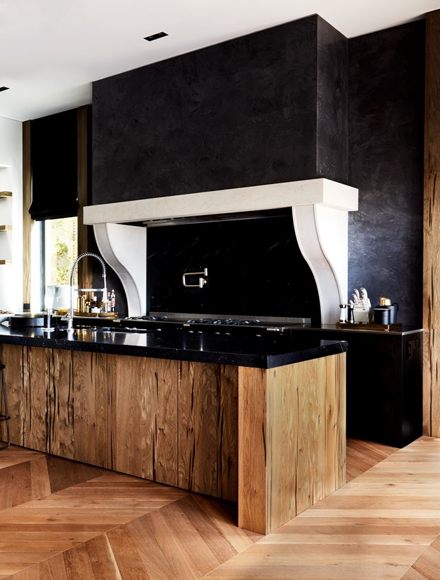A decorative rangehood and island in Eveneer American oak veneer make this black kitchen a showstopper. *Photo: Prue Ruscoe*