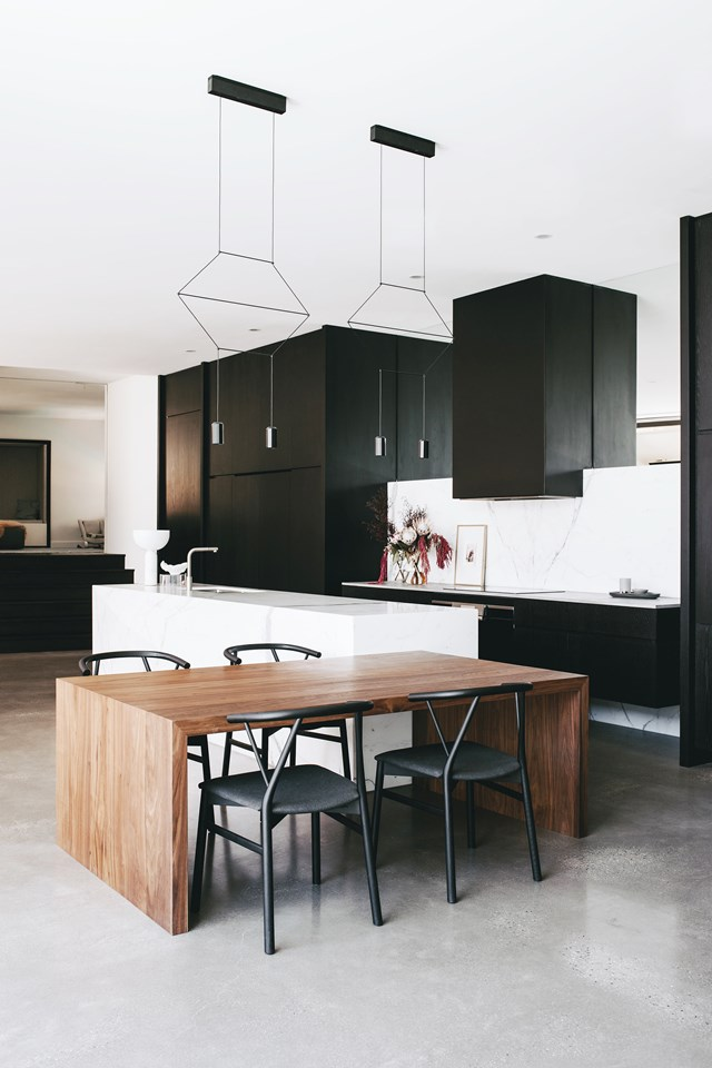 Balancing glamour and durability was the key design driver for this black kitchen, which features concrete flooring, matte-lacquered oak cabinetry and statement marble for the island and splashback. *Photo: Christopher Morrison*