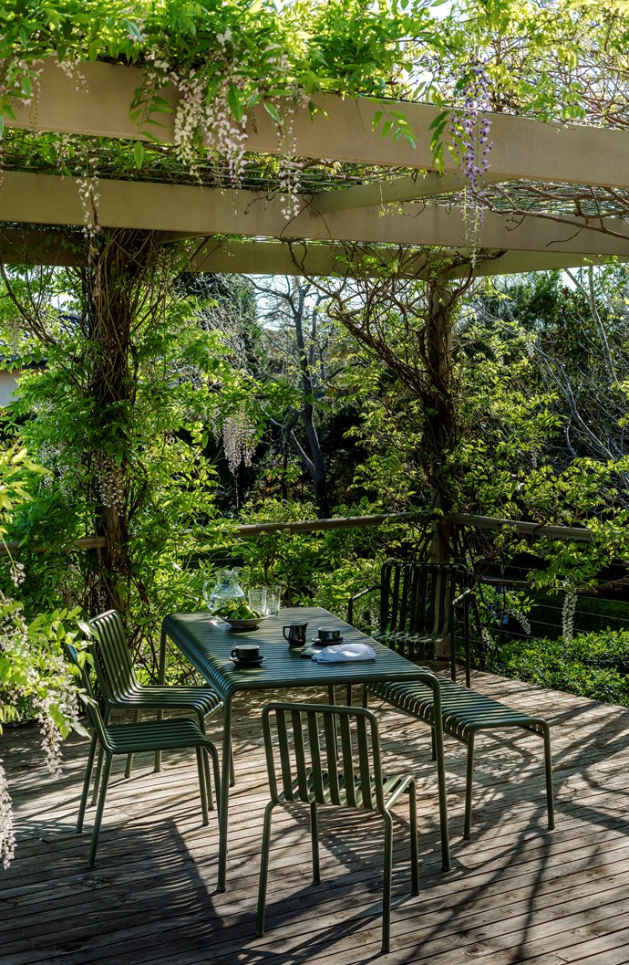 """""""The awkward sloping site demanded a terraced layout, and the change of levels provide so much more interest."""" The deck provides a transition between the house and the garden, and is constantly in use for dining and entertaining. The pergola is covered in vines year round, and wisteria blooms in spring."""